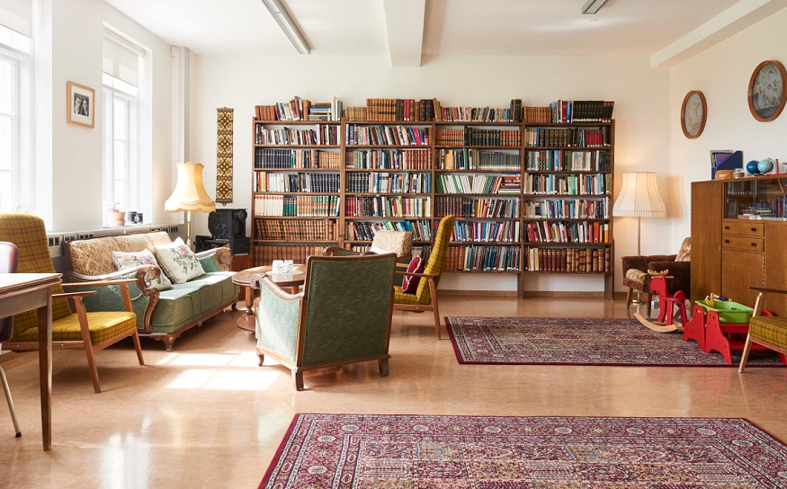 best places to see the northern lights, sofas and bookshelves in héraðsskólinn hostel