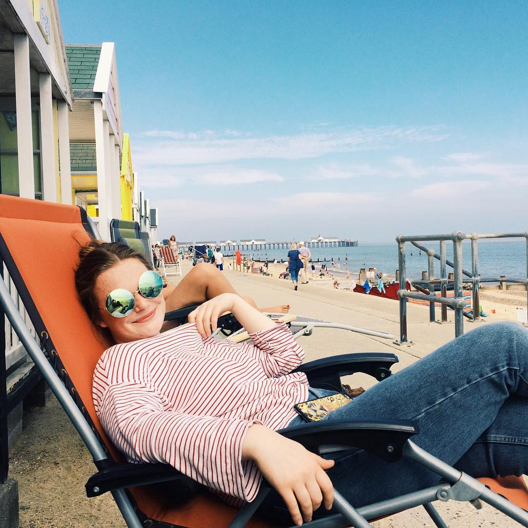 Relaxing on a deck chair by the beach in Southwold, Sussex