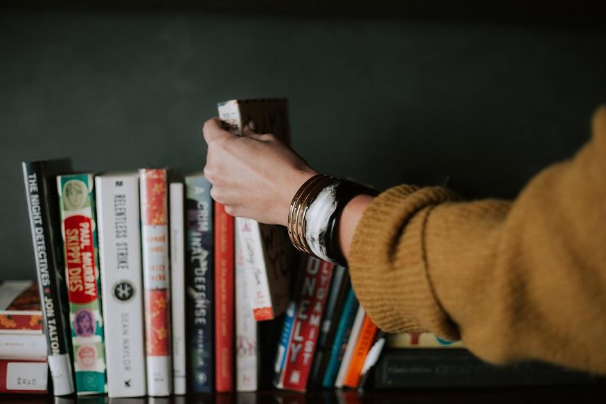 Best travel books - Picking a book on a shelf