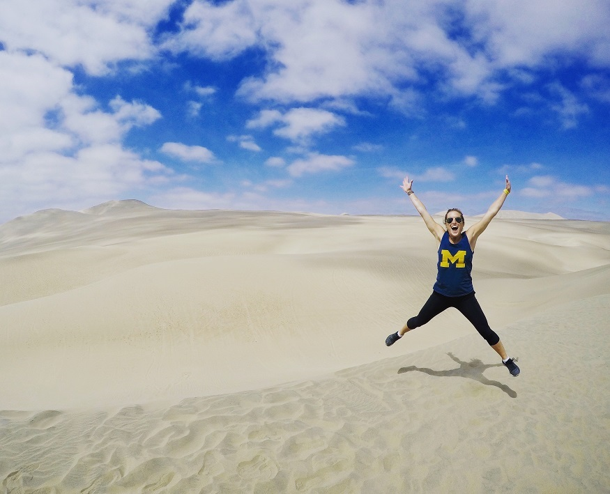 reasons why women travel solo - girl jumping by sand
