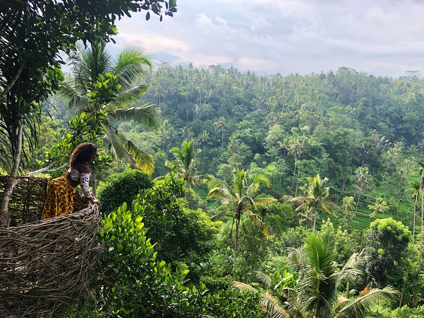 reasons why women travel solo - girl looking out over bali jungle