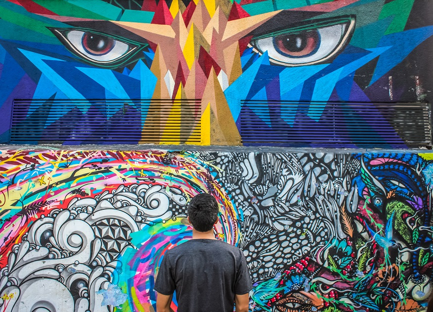 things to do in São Paulo - man looking at graffiti wall - graffiti eyes