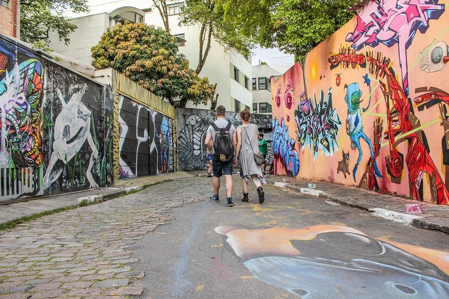 things to do in são paulo - street art in beco do batman - couple walking down street covered in street art