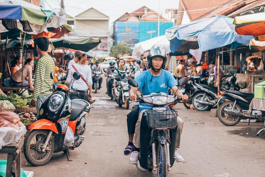 Siem Reap Sehenswürdigkeiten - Mann auf Moped fährt durch den Markt