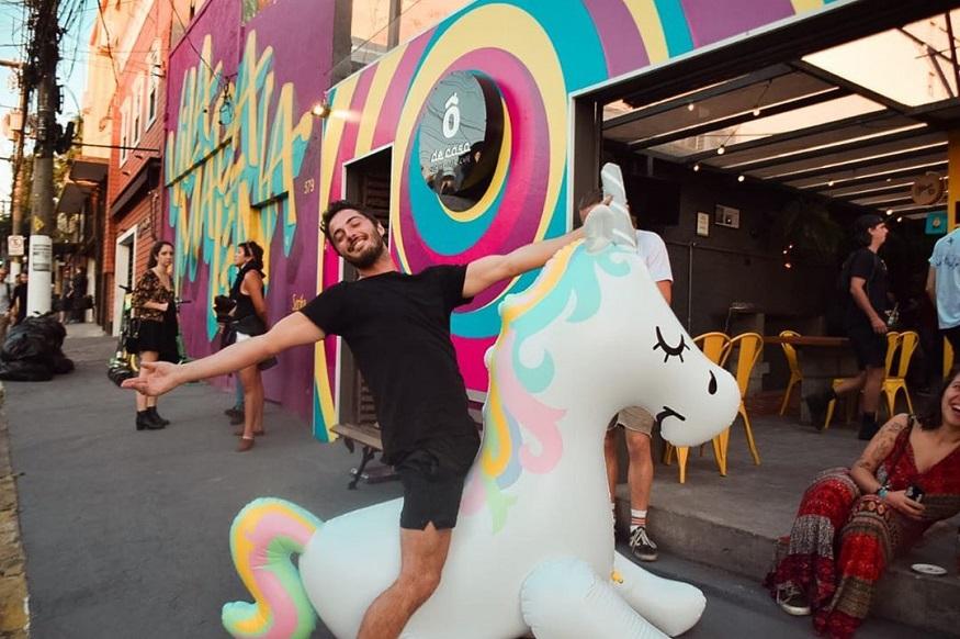 20 year anniversary stories, man sitting on unicorn at o de casa hostel bar,são paulo