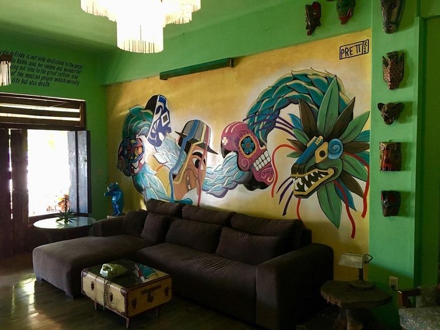eco-friendly hostels, El Jardin de Frida hostel social area with sofa and graffiti on wall