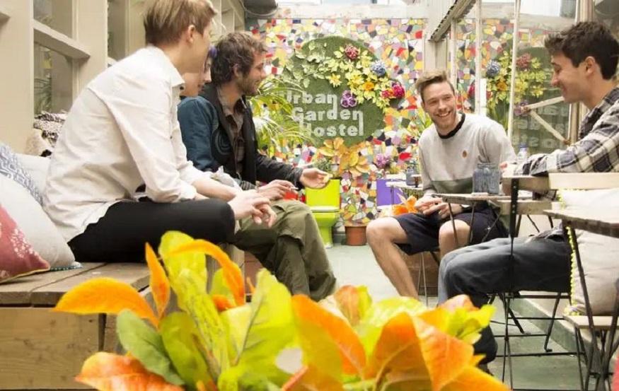 eco-friendly hostels, people sitting in outdoor terrace at urban garden hostel