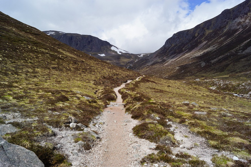 scotland road trip, path surrounded by mountains through cairngorms national park