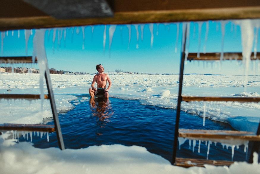 visiter helsinki - homme assis sur la glace après un sauna