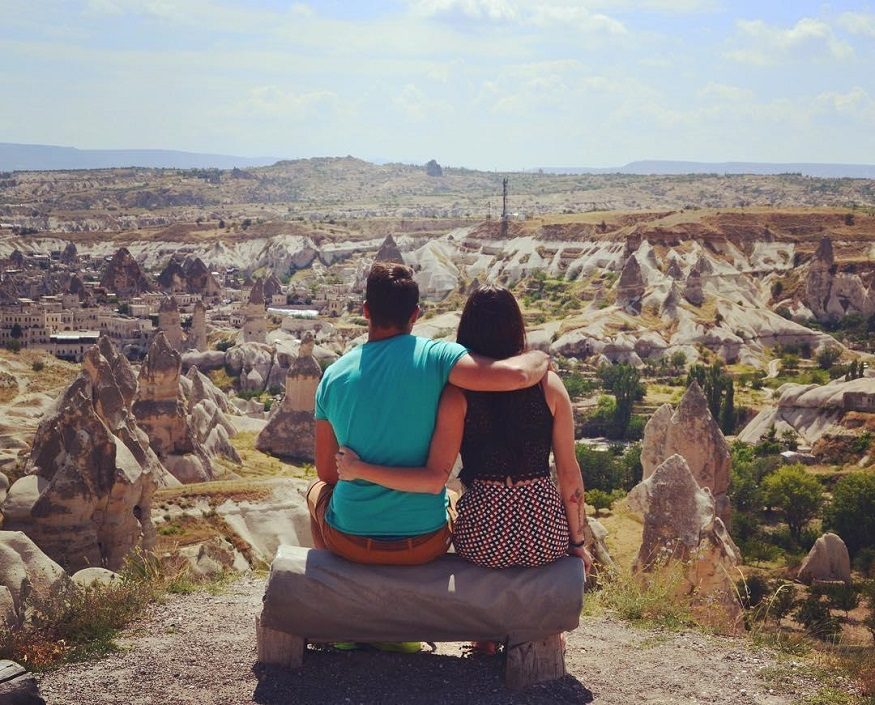 best national parks in europe, two people sitting on a bench overlooking göreme national park, turkey