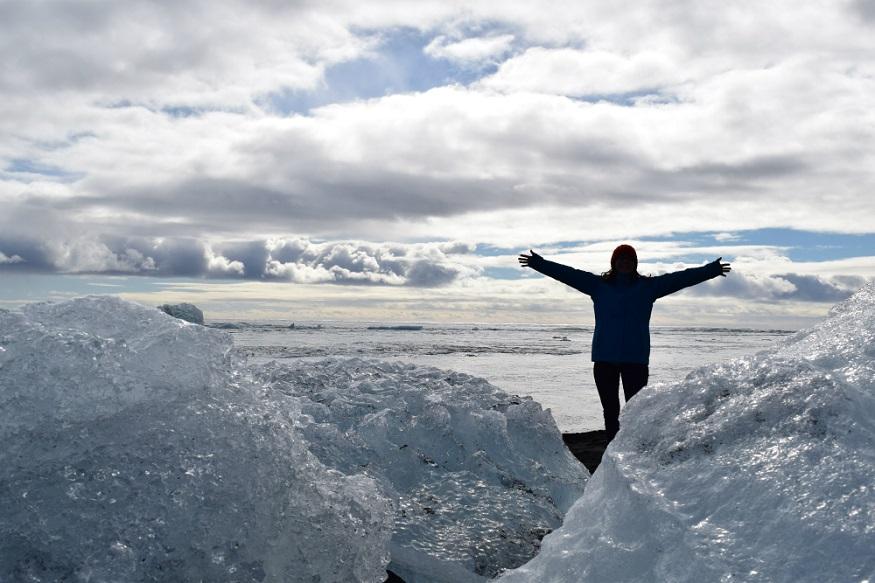 best national parks in europe,girl standing by a glacier in vatnajökull national park, iceland