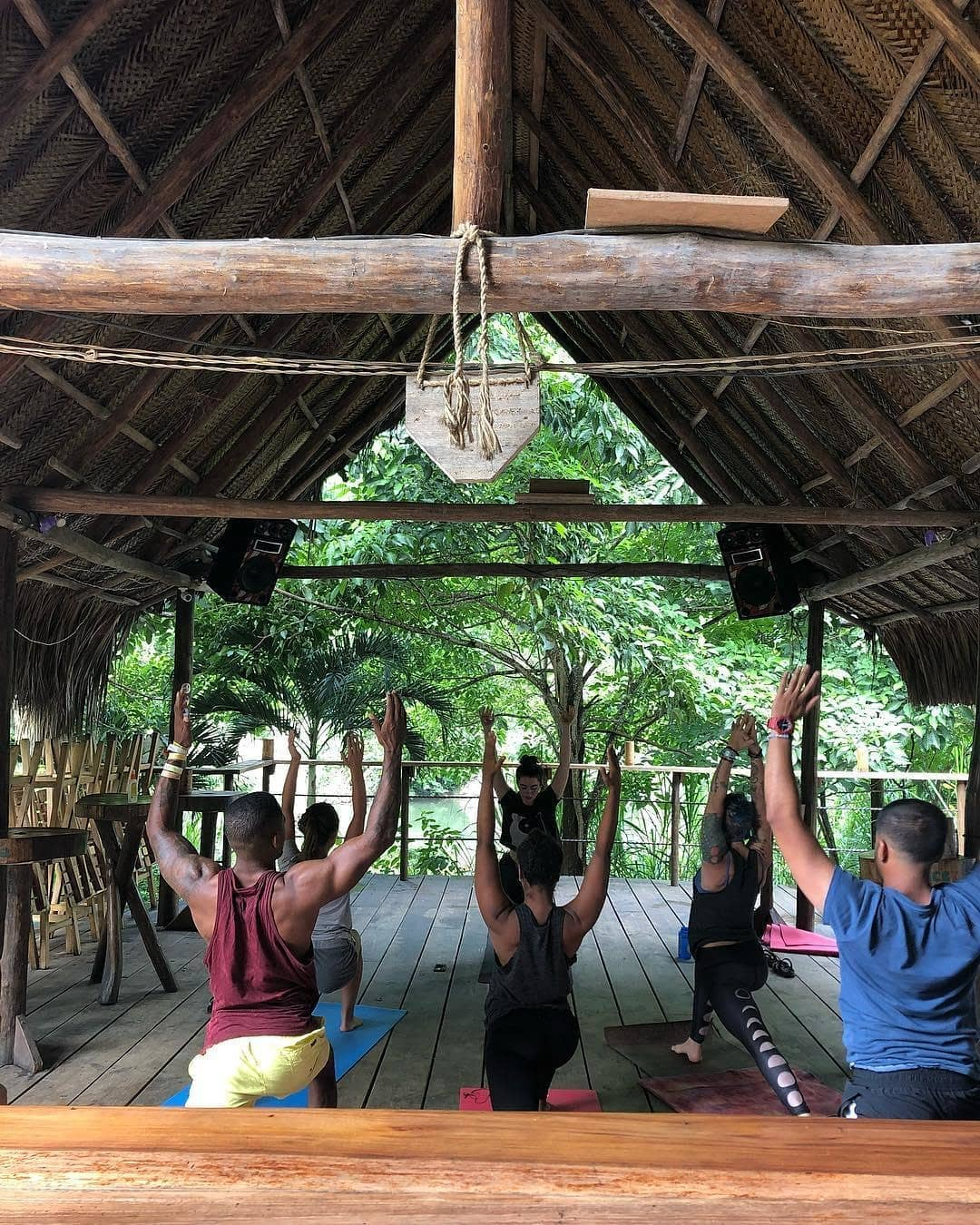 how to avoid overtourism, people doing yoga in a wooden shack
