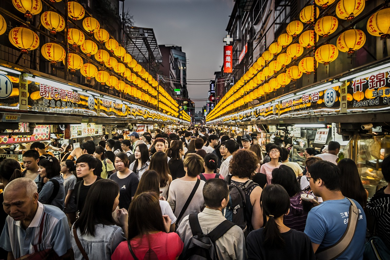 how to avoid overtourism, crowd of people walking down the street in asia