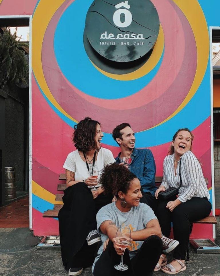 best independent hostels, people sitting with drinks outside Ô De Casa Hostel, São Paulo, Brazil