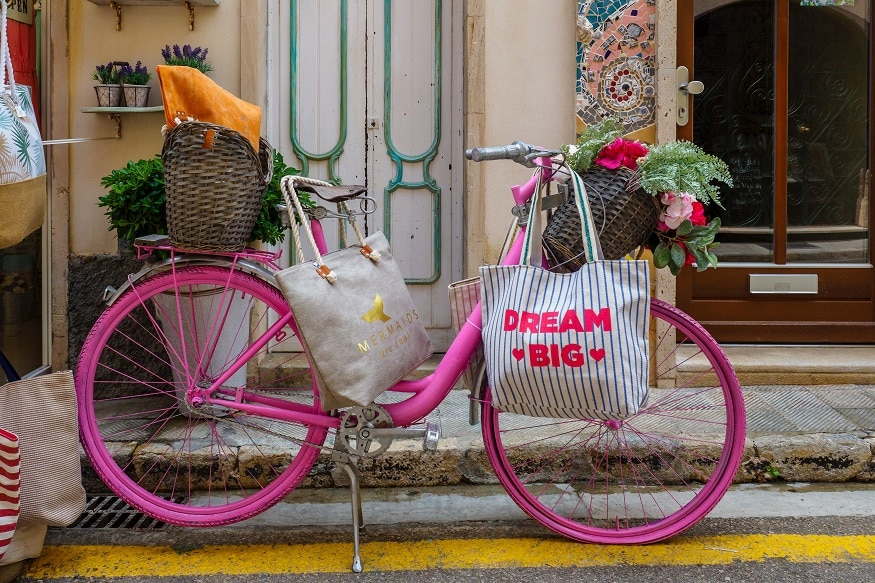 sustainable packing list, pink bike with bags