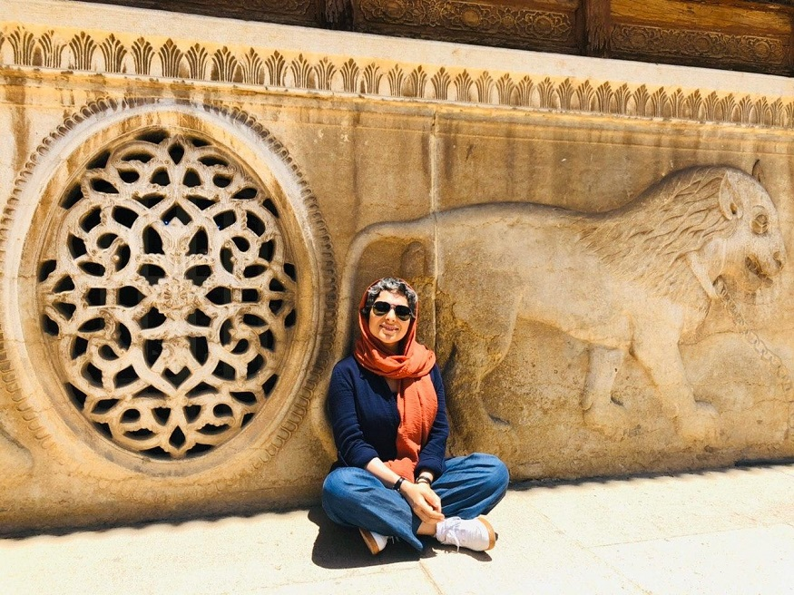 female hostel owners, girl sitting by wall with carved lion in Iran