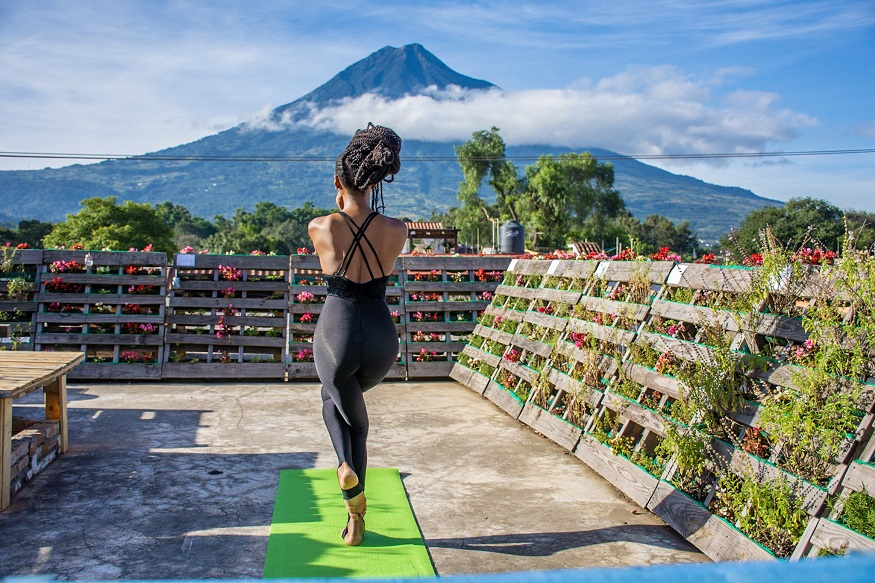 female hostel owners, woman doing yoga at The Purpose Hostel with mountain in the background