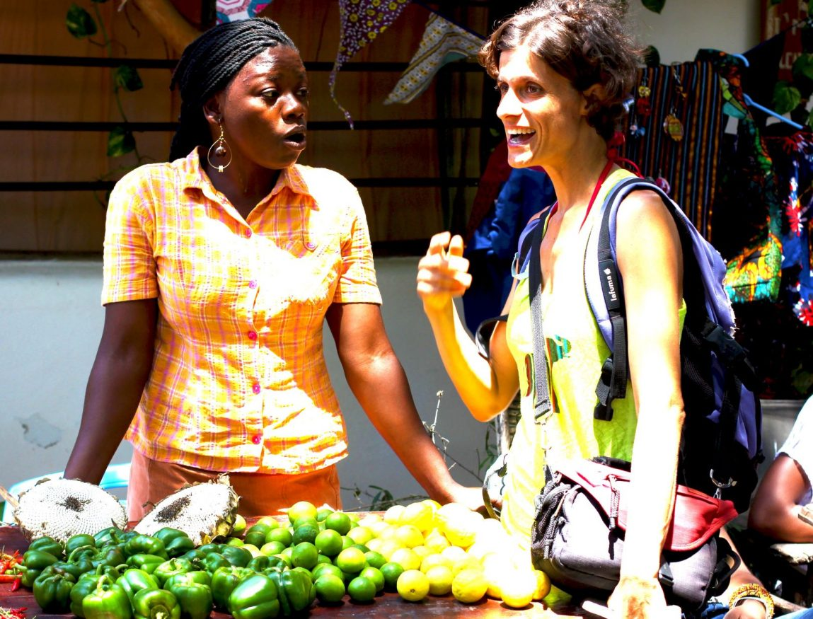 two women chatting by a fruit stand near Distant Relatives Ecolodge & Backpackers hostel ,nominated for extraordinary sustainable hostels