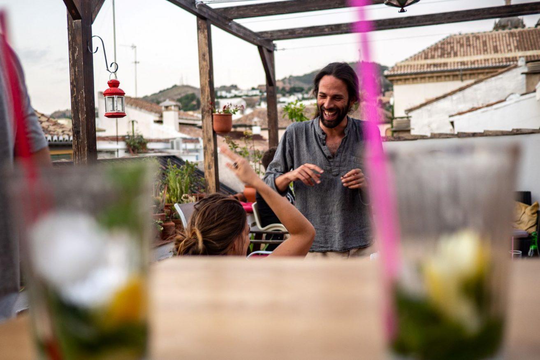 man laughing on rooftop bar at El Granado Hostel, nominated for extraordinary sociable experience hostels award